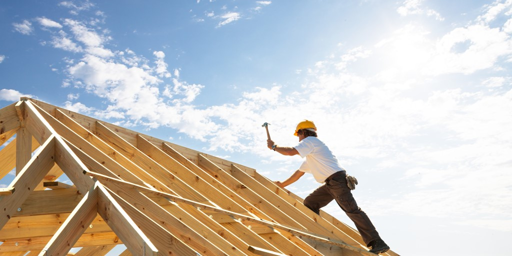 Carpenter working on a house roof frame